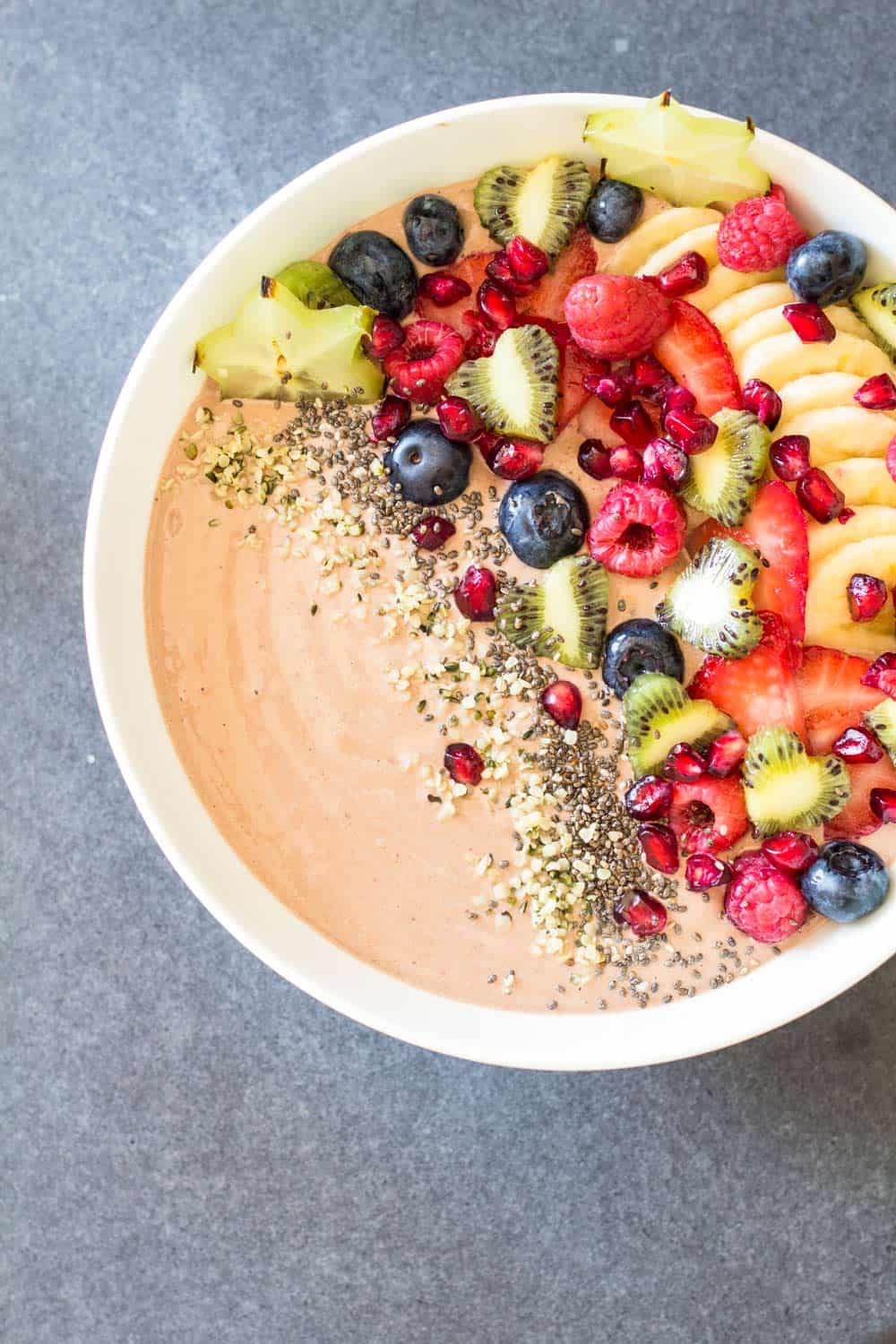 Top view of Chocolate Smoothie Bowl with chopped fresh fruit and seeds.