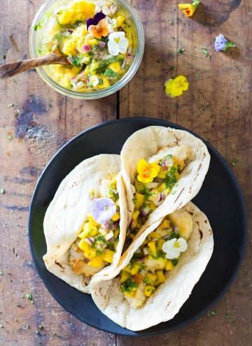 Top view of Easy Fish Tacos on a plate and a jar of Mango Salsa with a wooden spoon.