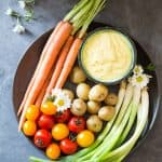 Top view of plate of fresh carrots, cherry tomatoes, green onions and baby potatoes, and a bowl of Huancaina dip.