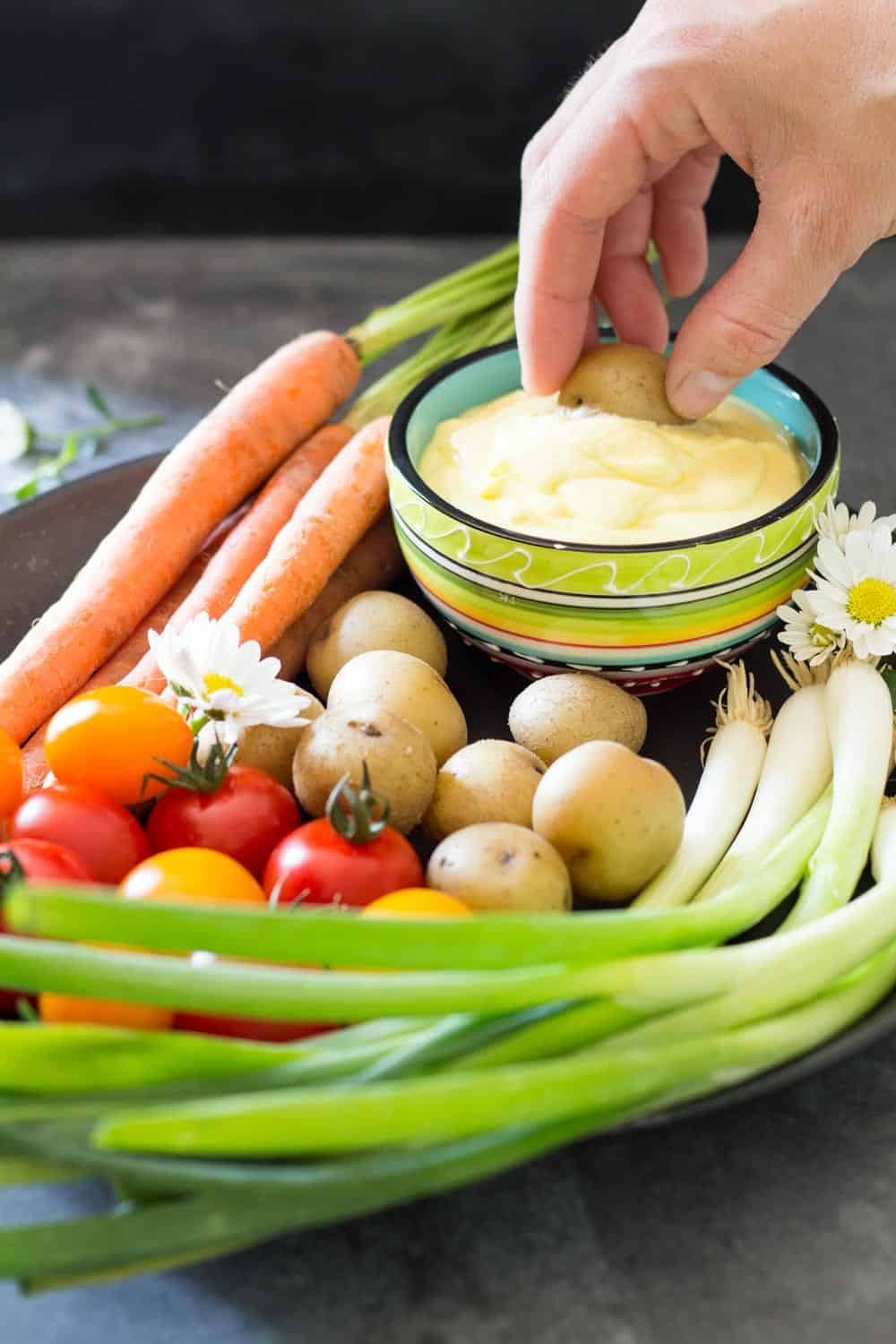 Plate of fresh carrots, cherry tomatoes, green onions and baby potatoes, and a hand dipping a potato into Huancaina dip.