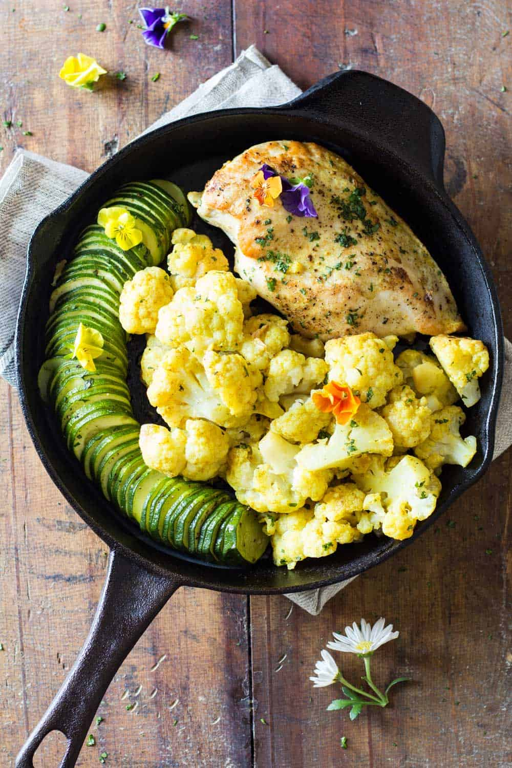 One-Pan Curried Chicken Cauliflower with sliced zucchini in a skillet.