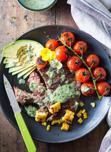 Skirt Steak with Basil Cream and Grilled Tomatoes, corn kernels and sliced avocado, a knife, and a jar of Basil Cream.