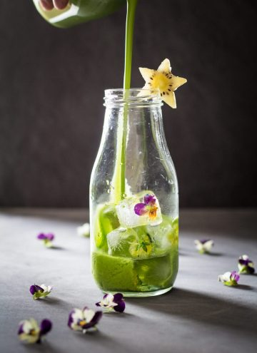 Green Smoothie being poured into a glass bottle decorated with a star-shaped kiwi slice.