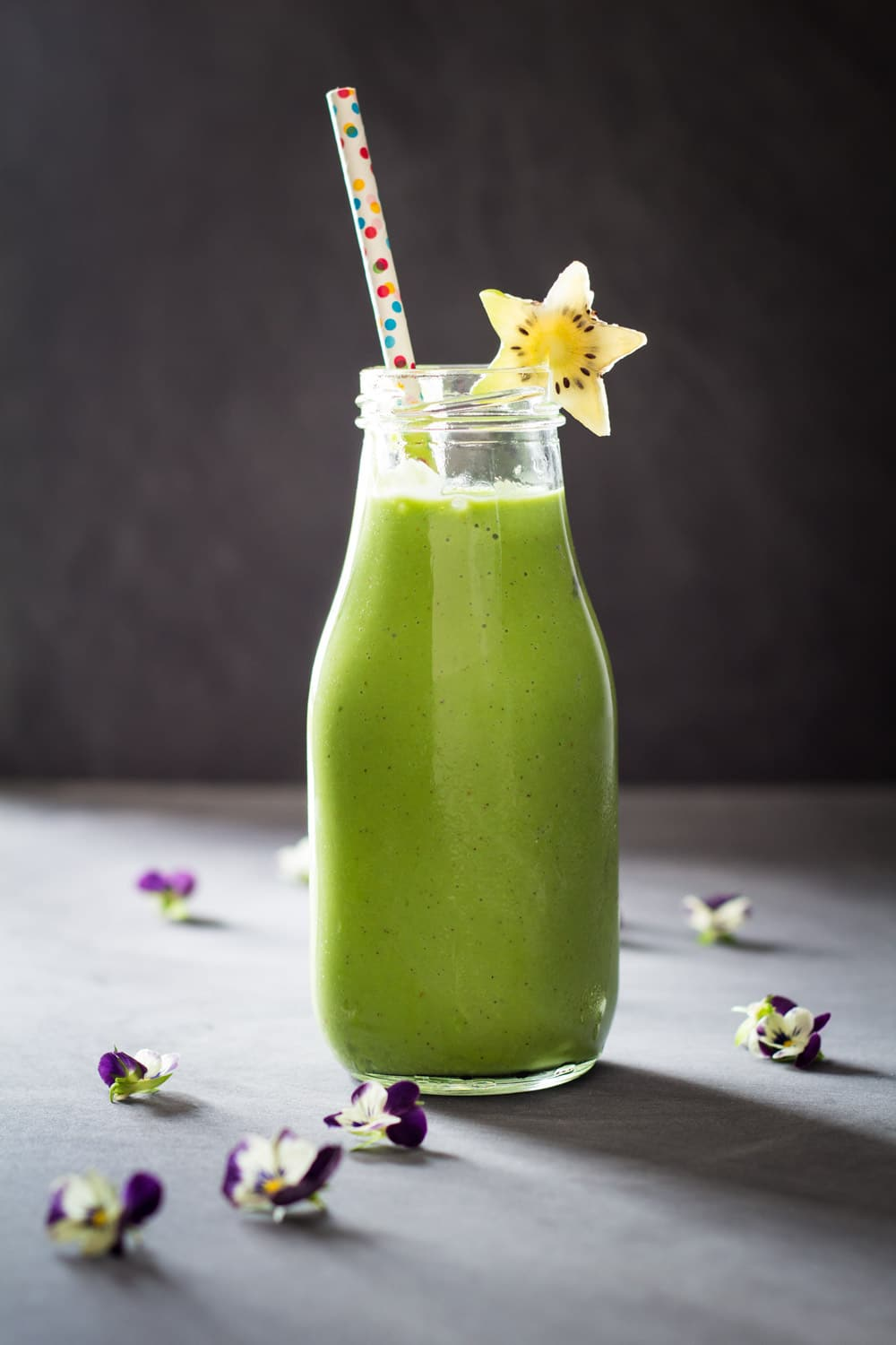 Green Smoothie For Kids in a glass bottle with a confetti straw and a star-shaped kiwi slice.