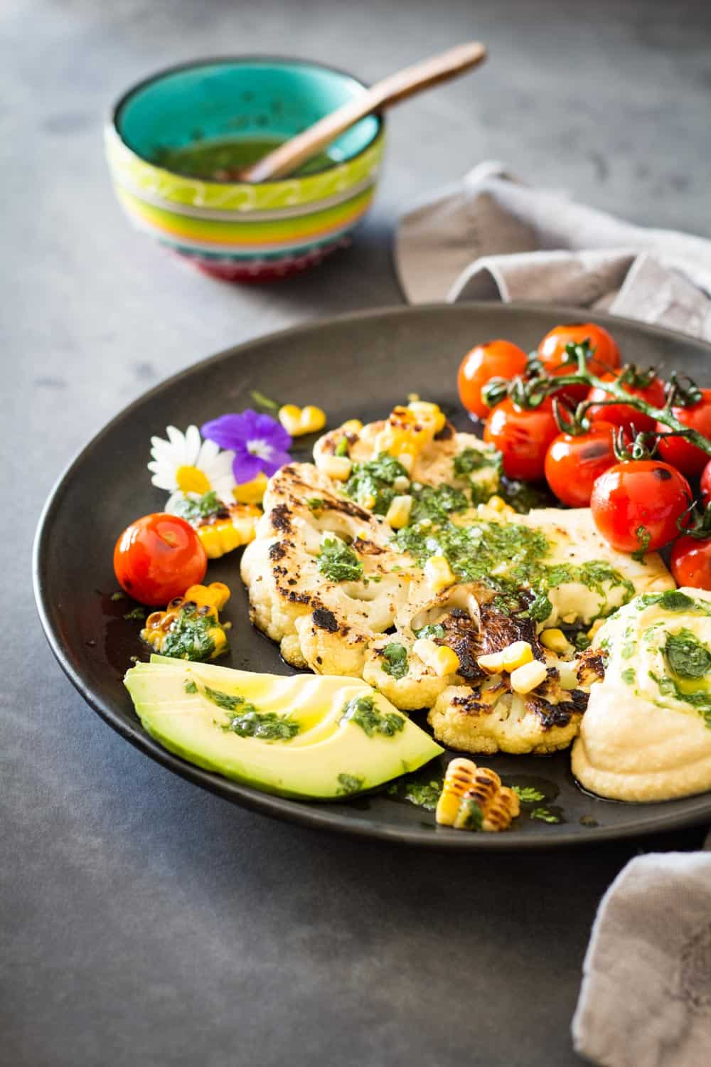 Grilled Cauliflower Steak with chimichurri sauce, cherry tomatoes and avocado on a plate, and a bowl of chimichurri sauce in the back.