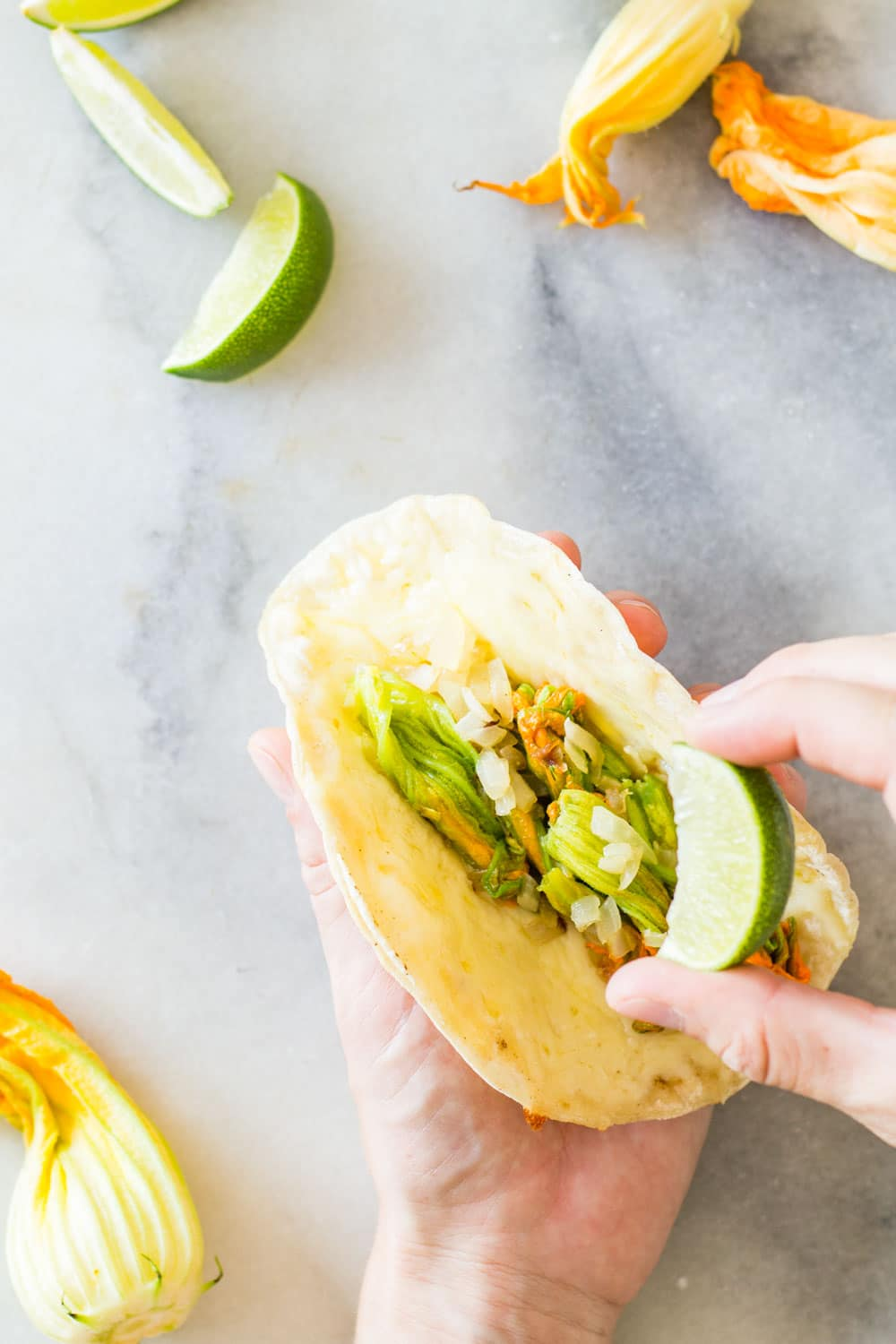 Hand holding a Squash Blossom Quesadilla and squeezing a lime on it.