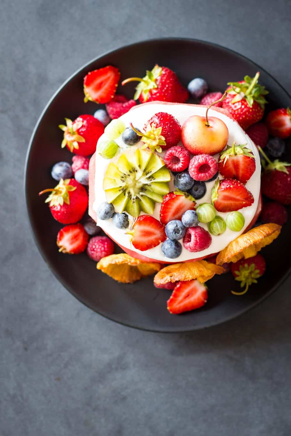 Top view of Vegan Watermelon Cake on a black plate decorated with fresh fruit.
