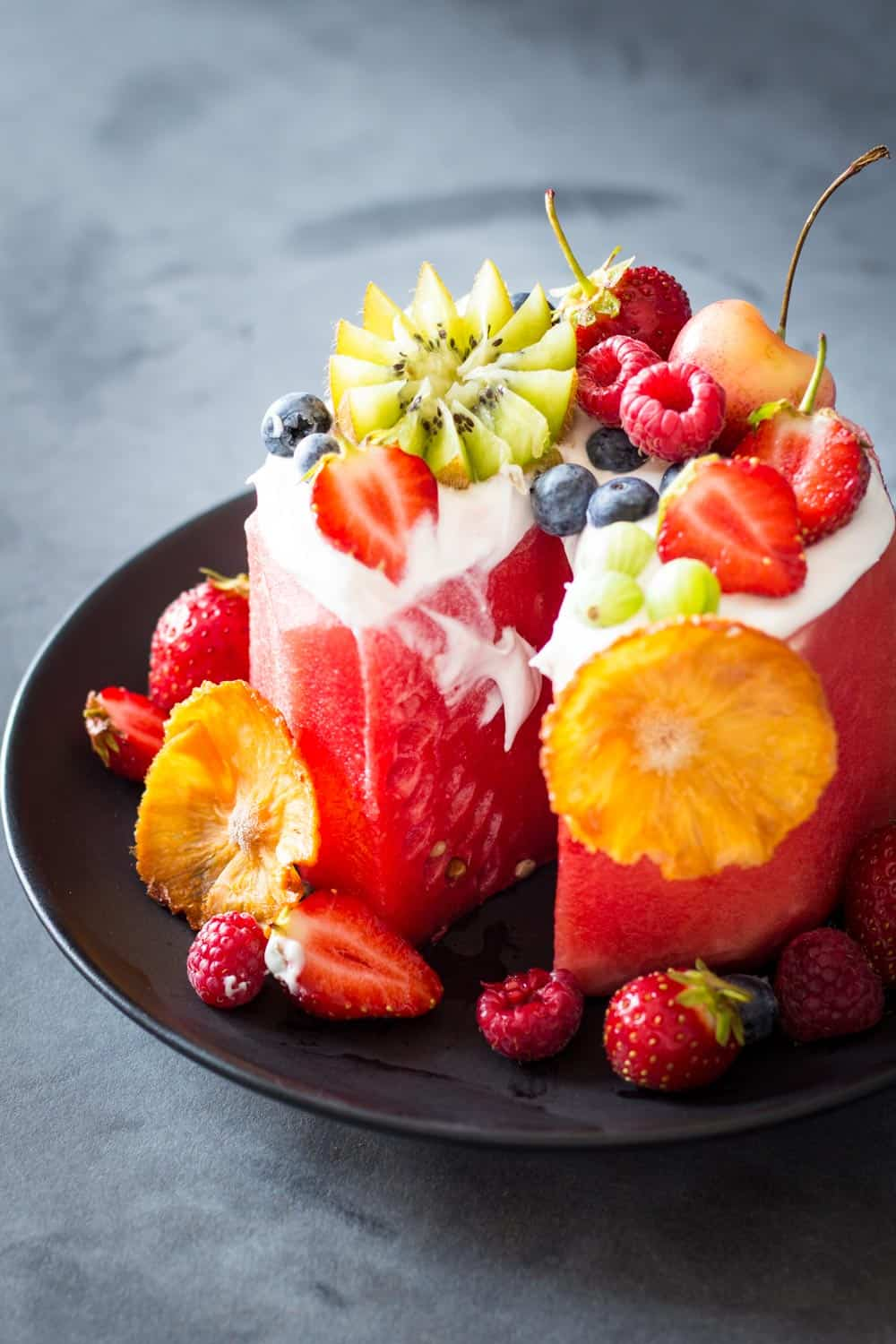 Sliced Vegan Watermelon Cake on a black plate decorated with fresh fruit.