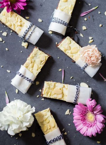 Top view of Almond Granola Bars laid out on a grey counter with fresh flowers.
