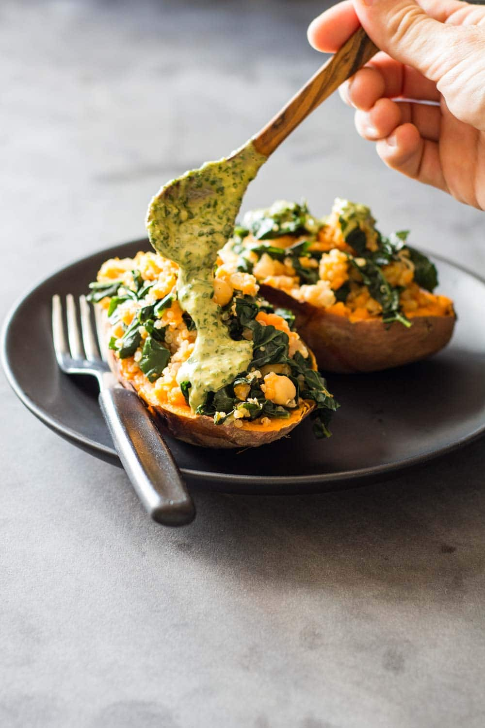 Tahini Herb Sauce being drizzled on healthy stuffed sweet potatoes