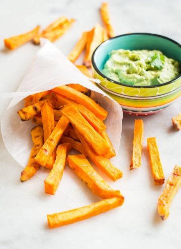 Sweet potato fries in a paper cone and Avocado Tahini Dip in a coloured bowl.