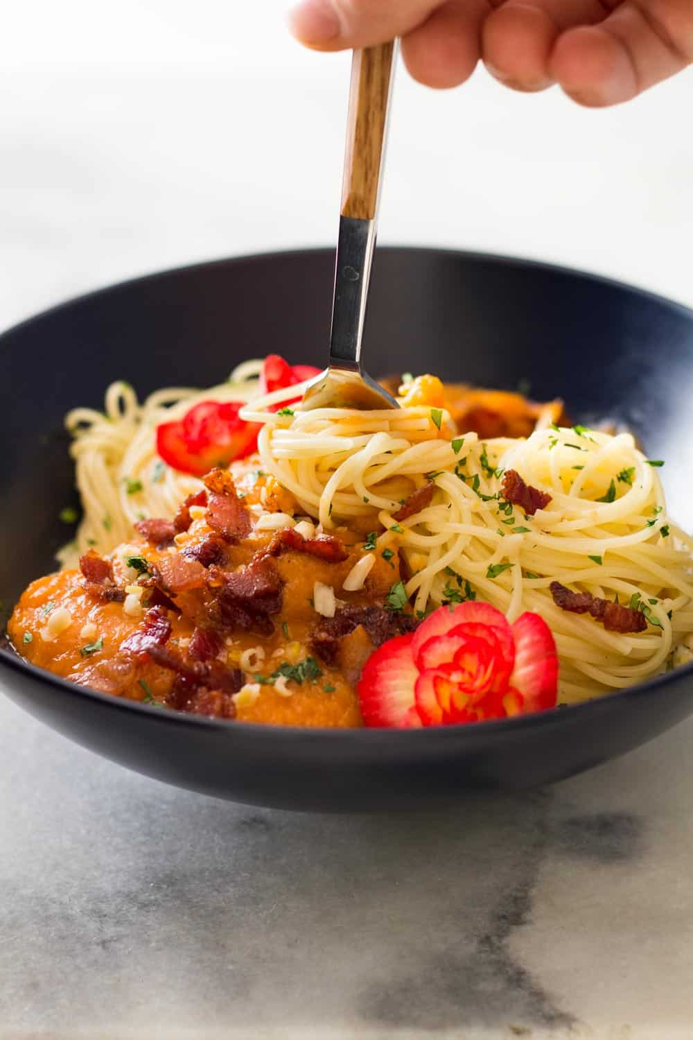 Hand grabbing spaghetti with a fork from a Butternut Squash Pasta with Bacon bowl.