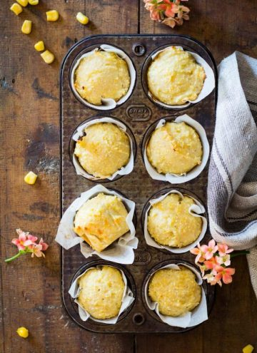 Cornbread muffins in parchment paper in a muffin tin.