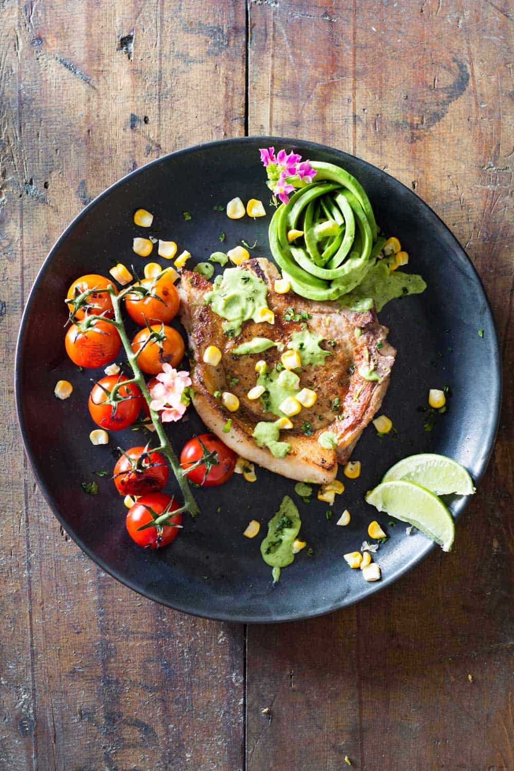 Mexican Pork Chops garnished with avocado cilantro sauce, corn kernels, cherry tomatoes and sliced lemon on a black plate.