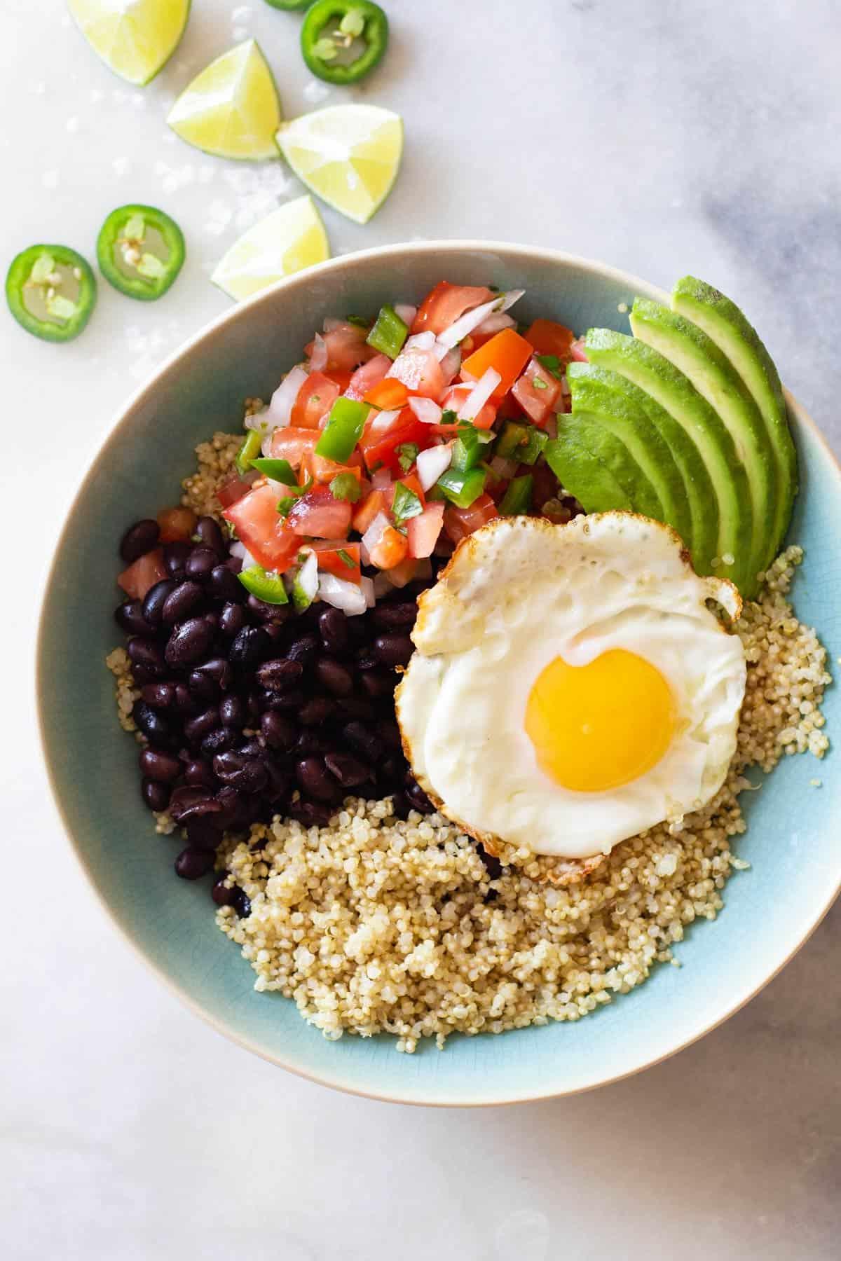 quinoa, black beans, fried egg, pico de gallo, sliced avocado in a blue bowl.