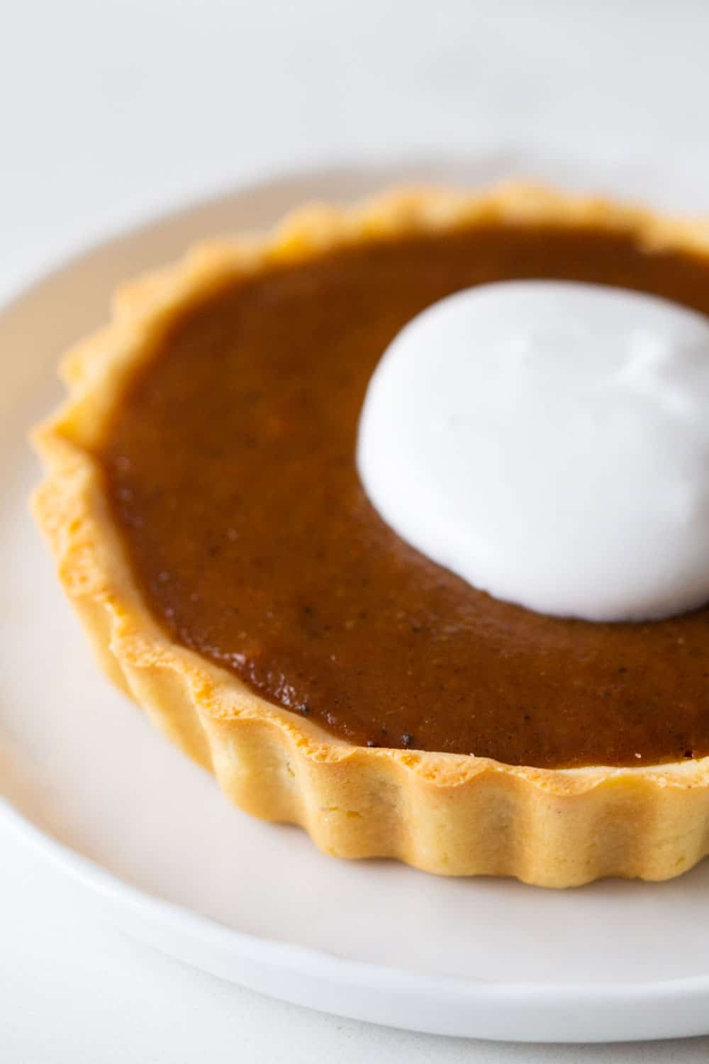 Close up of pumpkin pie with whipped cream on top.