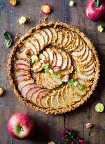 Top down view of baked apple tart on a rustic wood board and fresh apples.