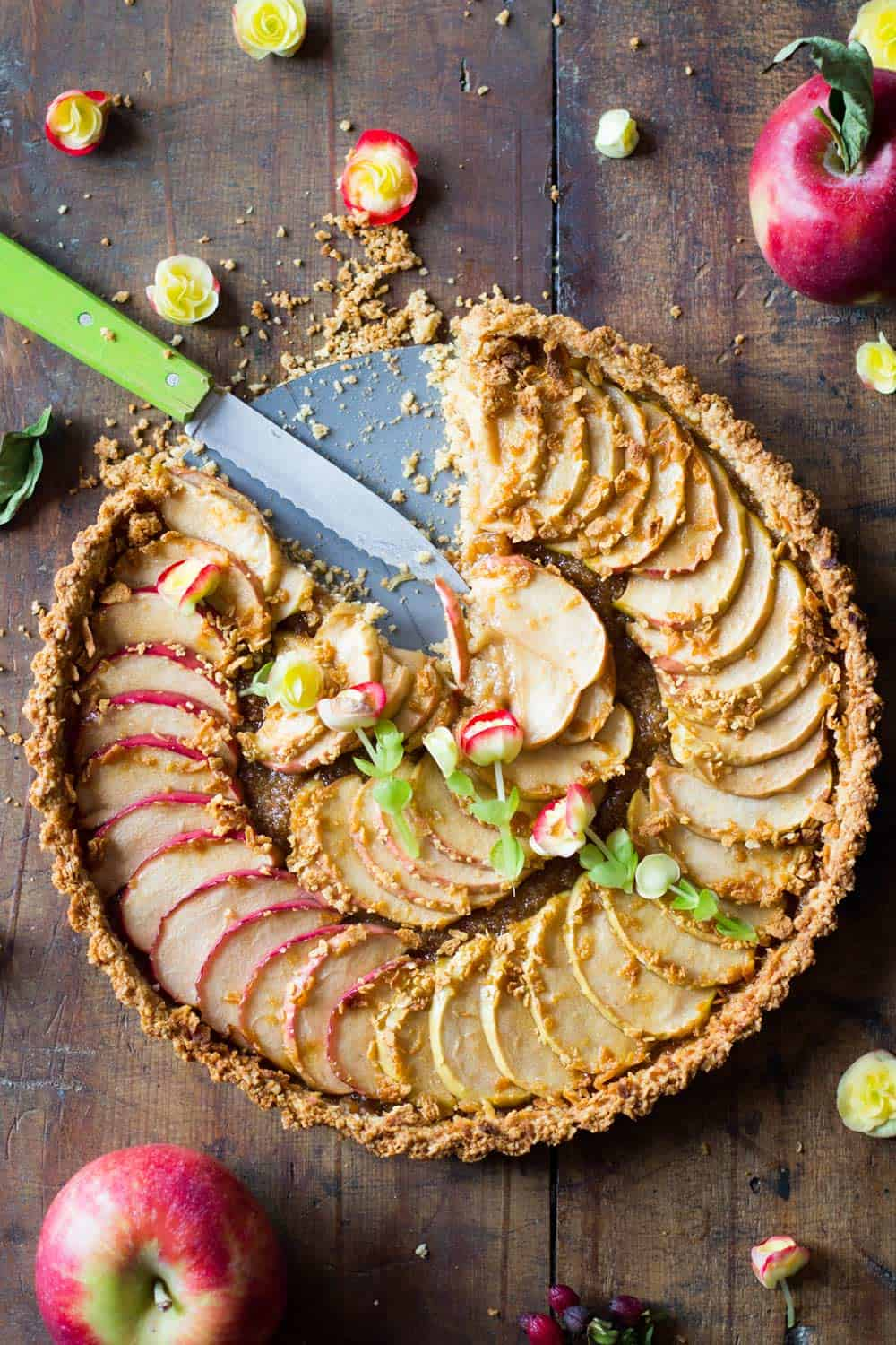 Top down view of baked apple tart missing a slice, and a cutting knife.