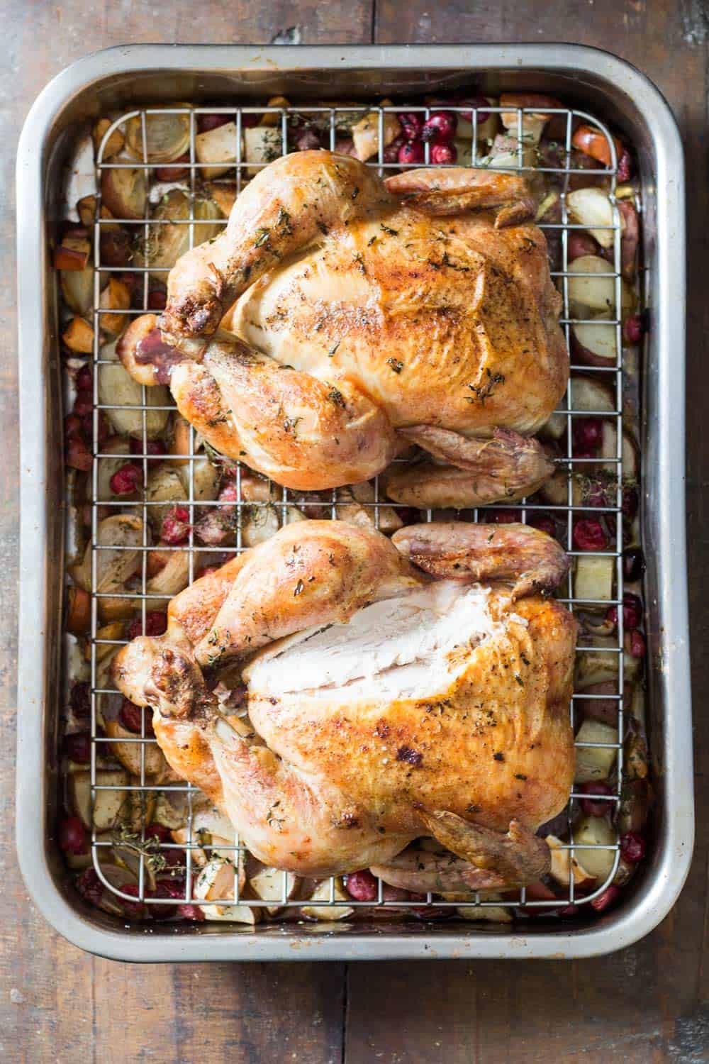 Two whole roasted chickens in grilling pan, with chopped apples, potatoes and cranberries at the bottom.