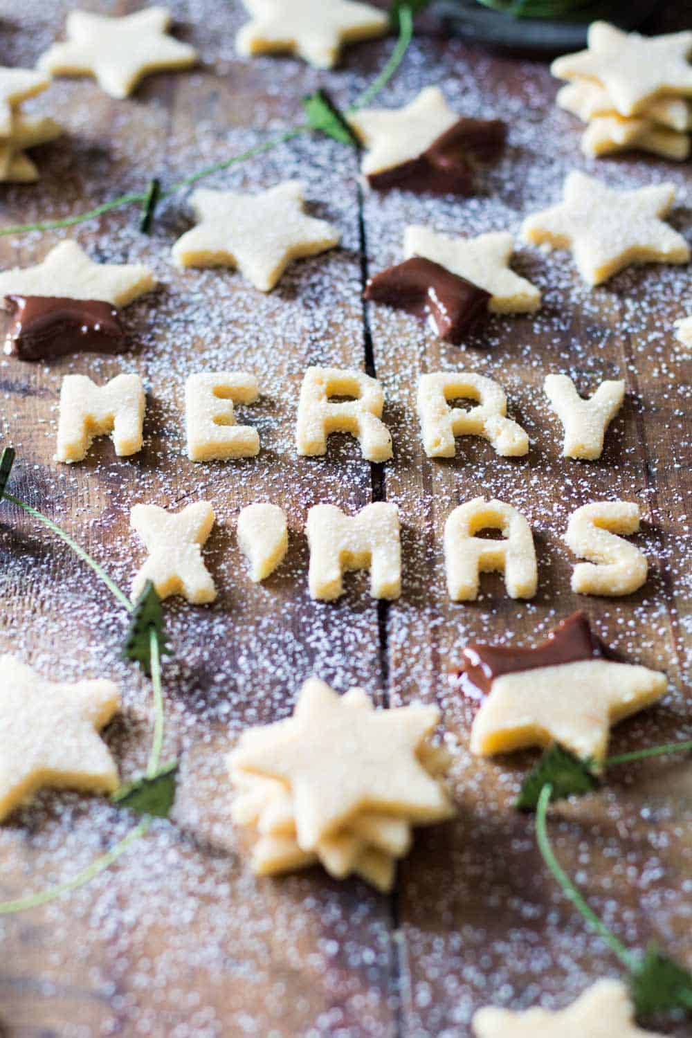 Star-shaped almond flour cookies scattered on wood board, and Merry X'mas sign made of almond flour.