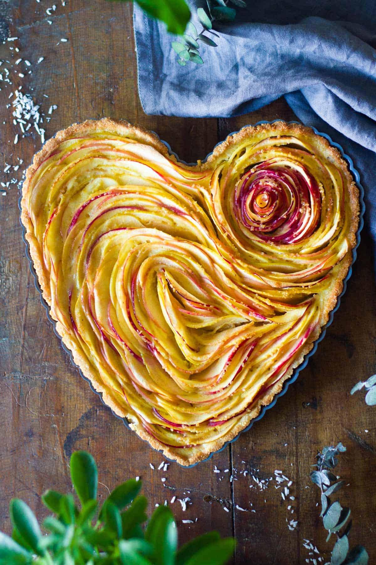 Baked apple tart in heart-shaped tart pan.