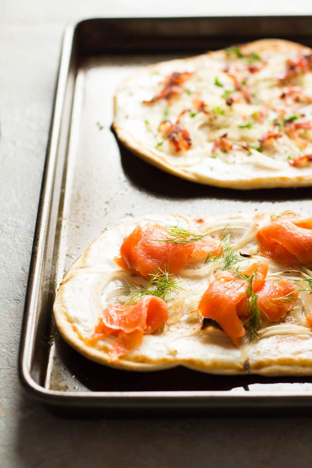 Detail of two flammkuchen. Top one with bacon and onions, bottom with smoked salmon, onions and dill, in a pan.