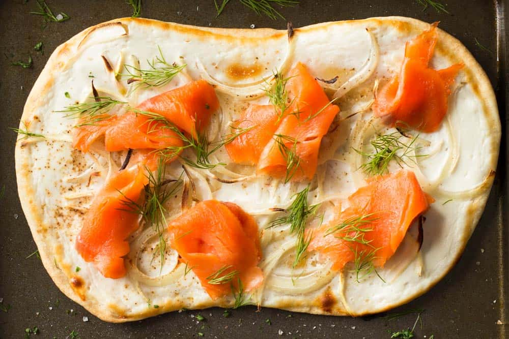 Top view of flammkuchen topped with smoked salmon, dill and onions.