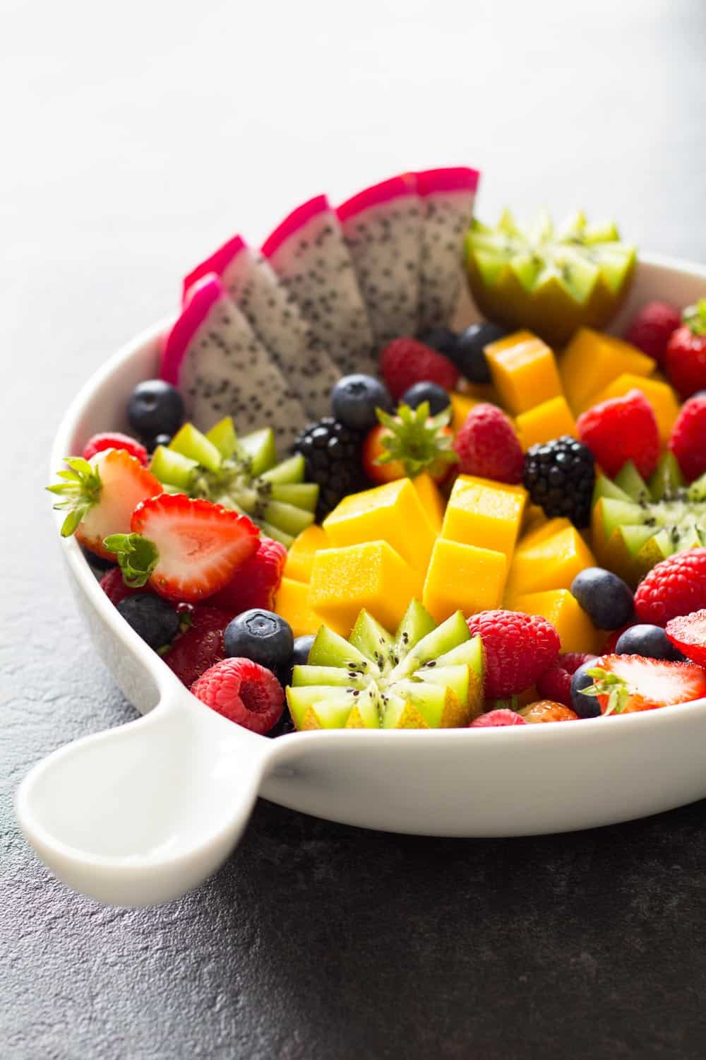 Fruit platter presented in a white bowl with a handle.
