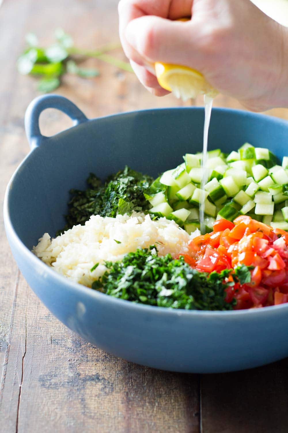 Cauliflower couscous with chopped parsley, diced cucumber and tomatoes in a blue bowl, with a hand squeezing a lime over it.