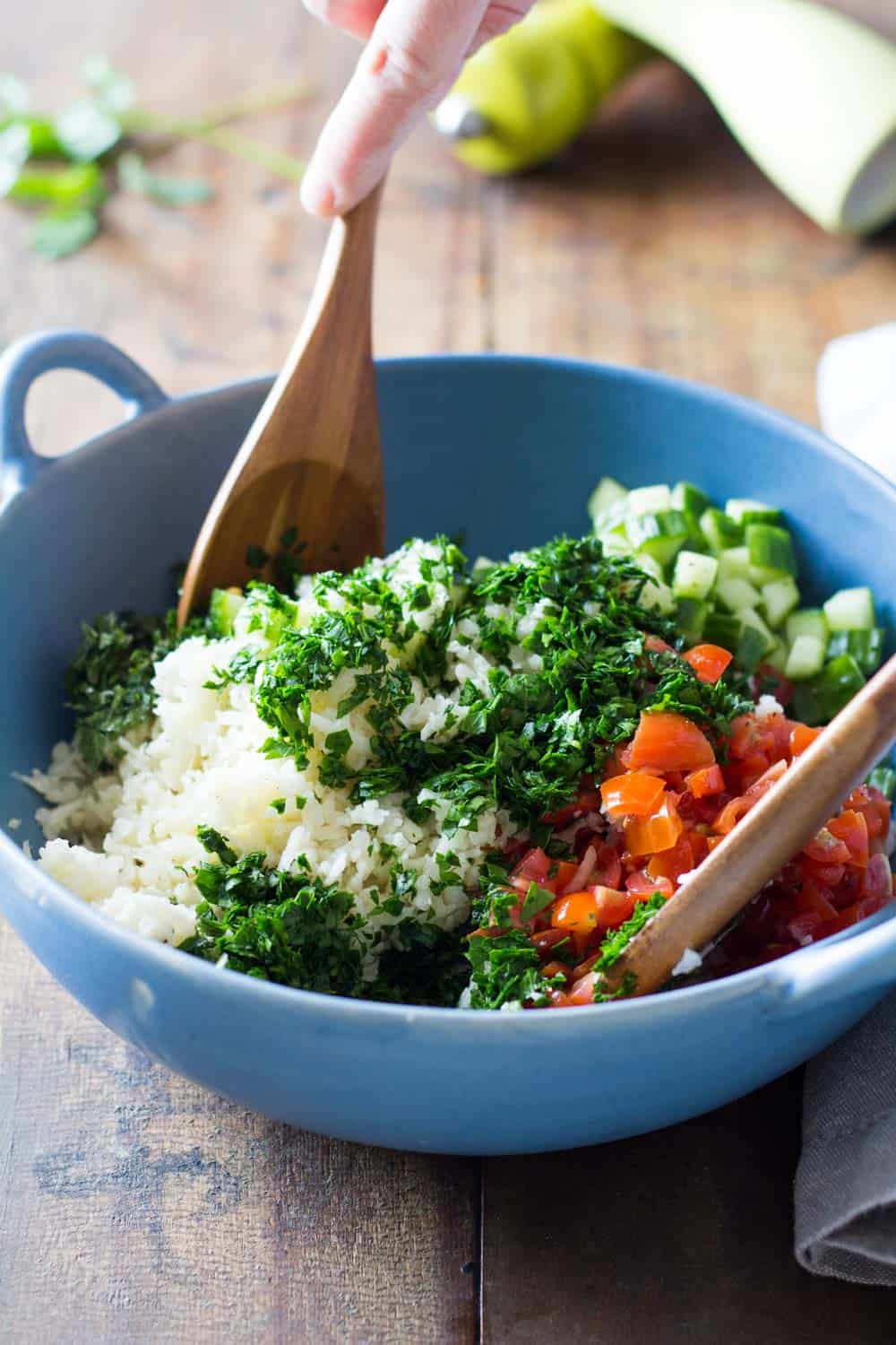 Cauliflower couscous tabbouleh salad being stirred with wooden spoons in a blue bowl.
