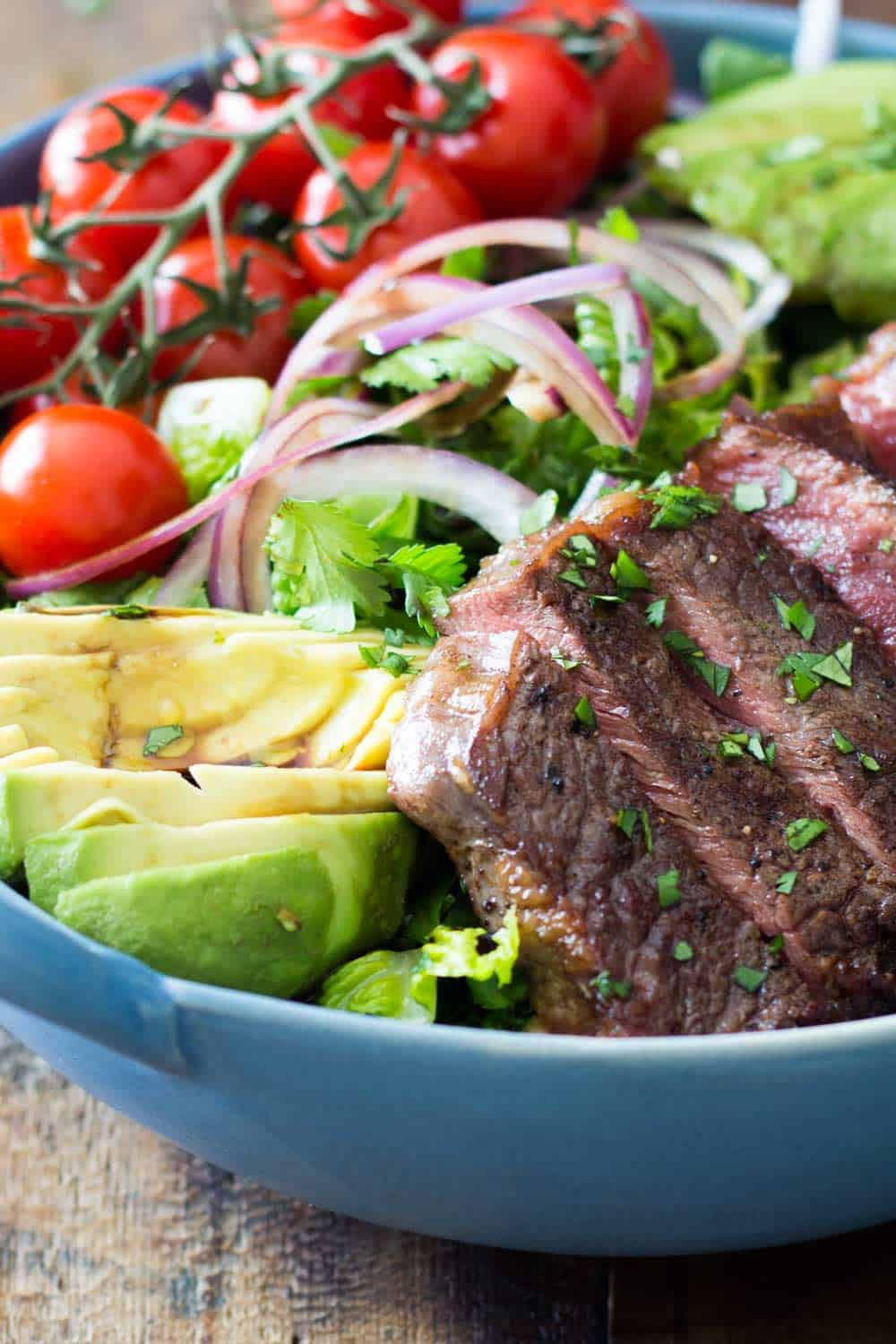 Strip loin steak salad with avocado, cherry tomatoes, cilantro and onions served in a blue bowl.