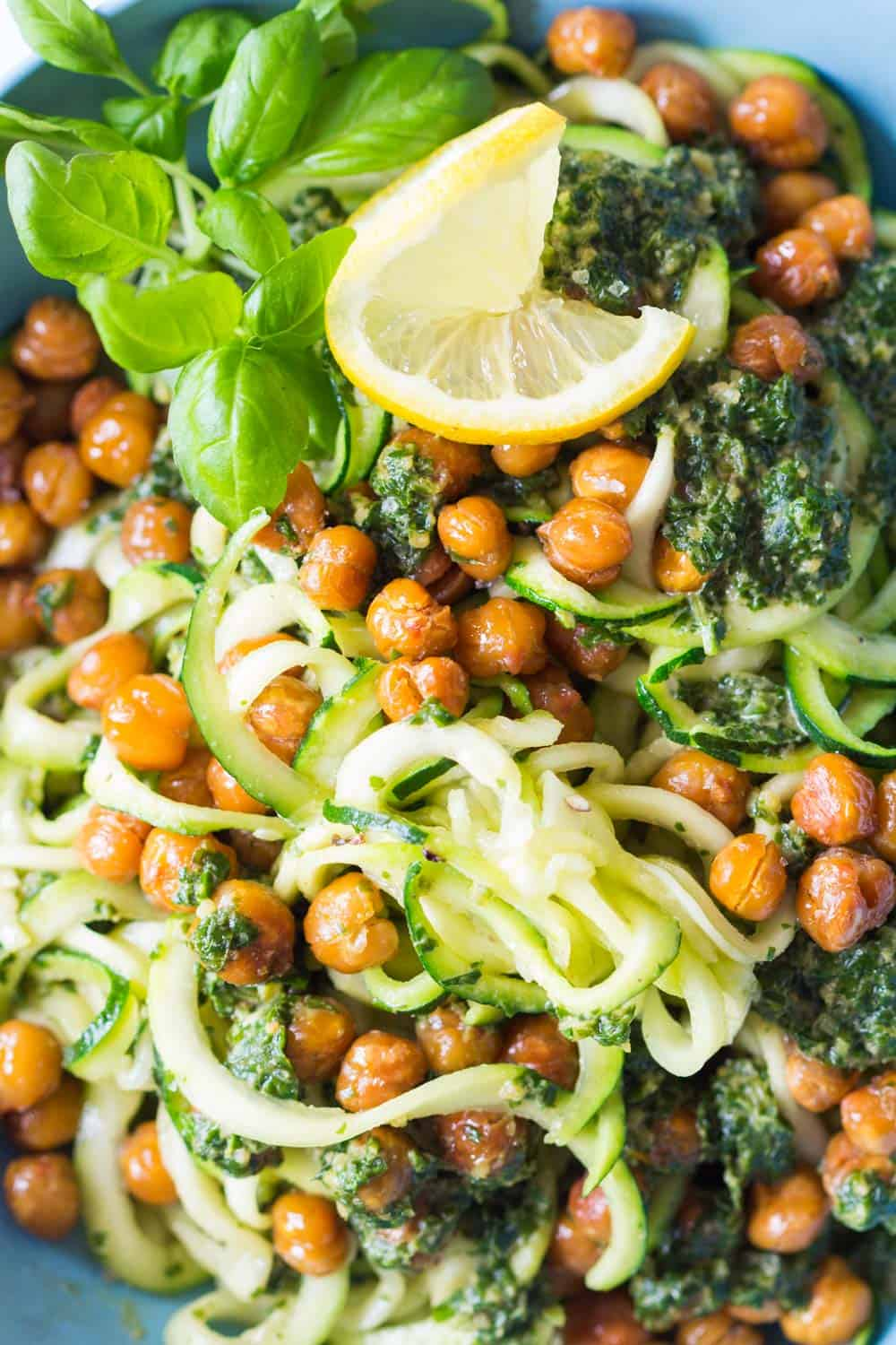 Zucchini noodles served with roasted chickpeas and tahini herb sauce, garnished with lemon slice and fresh basil leaves.