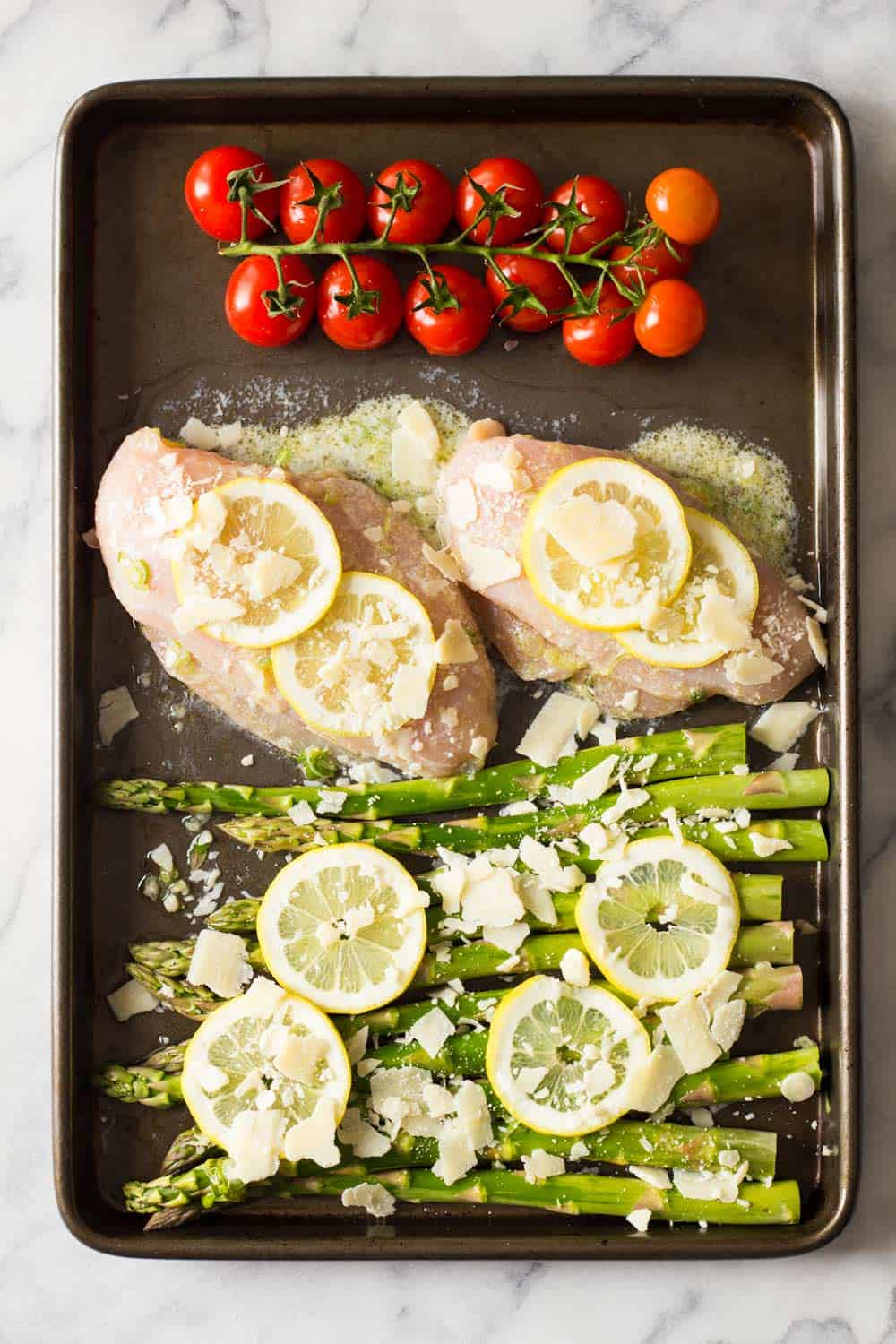 Sprig of cherry tomatoes, lemon chicken breasts and asparagus in a pan.