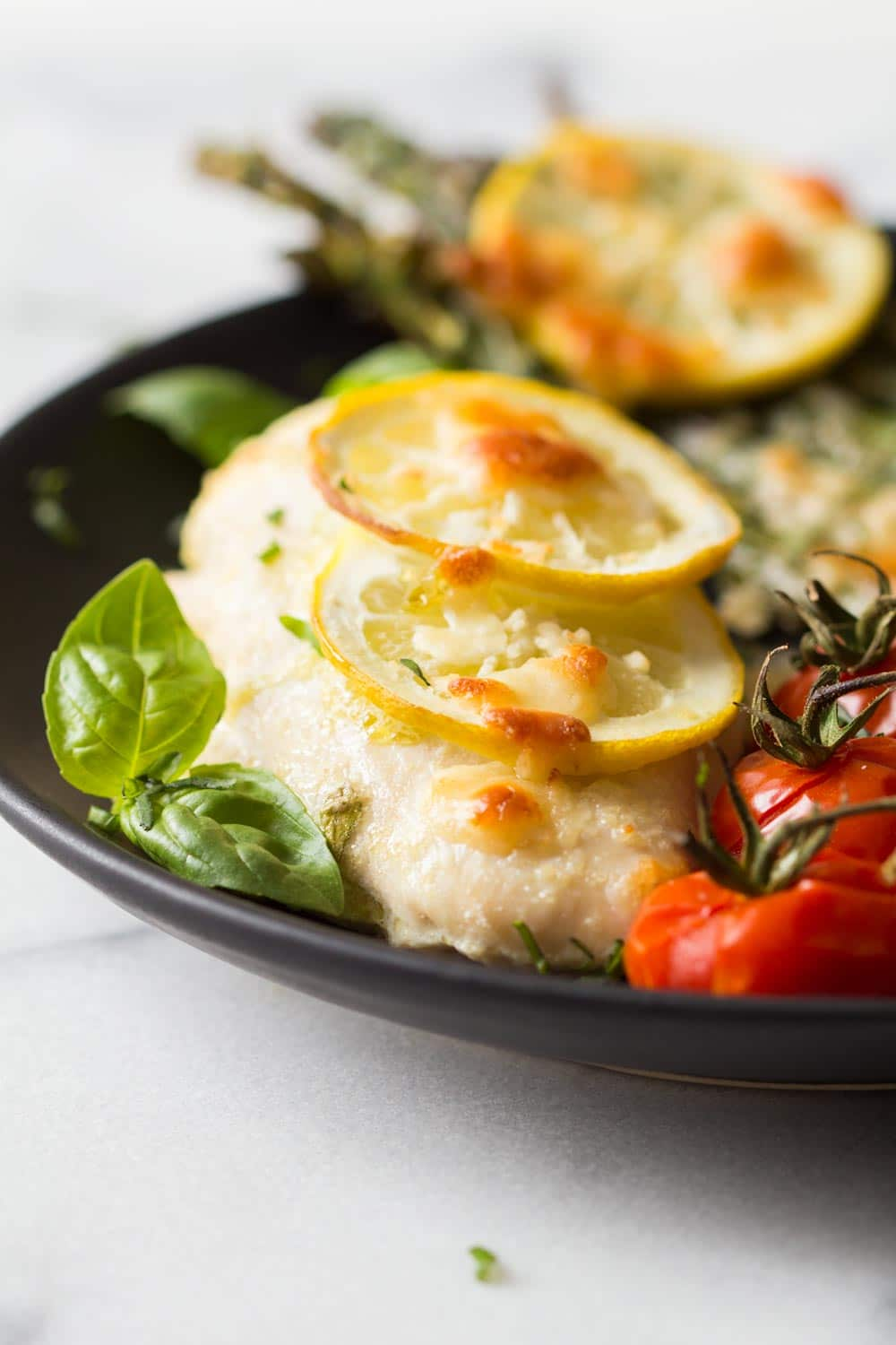 Detail of baked lemon chicken and asaparagus with cherry tomatoes, served on a black plate.