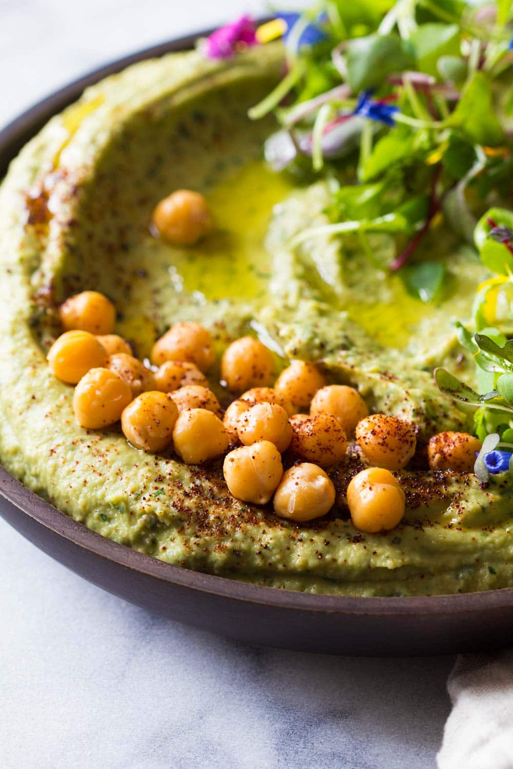 Spicy hummus and avocado presented in a bowl with whole chickpeas and lettuce leaves, sprinkled with chili powder.