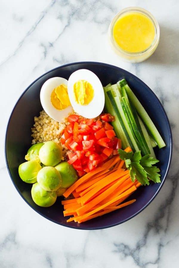 Instant Pot Quinoa Bowl with hard-boiled egg, cucumber, carrots, tomatoes, avocado and lemon tahini dressing