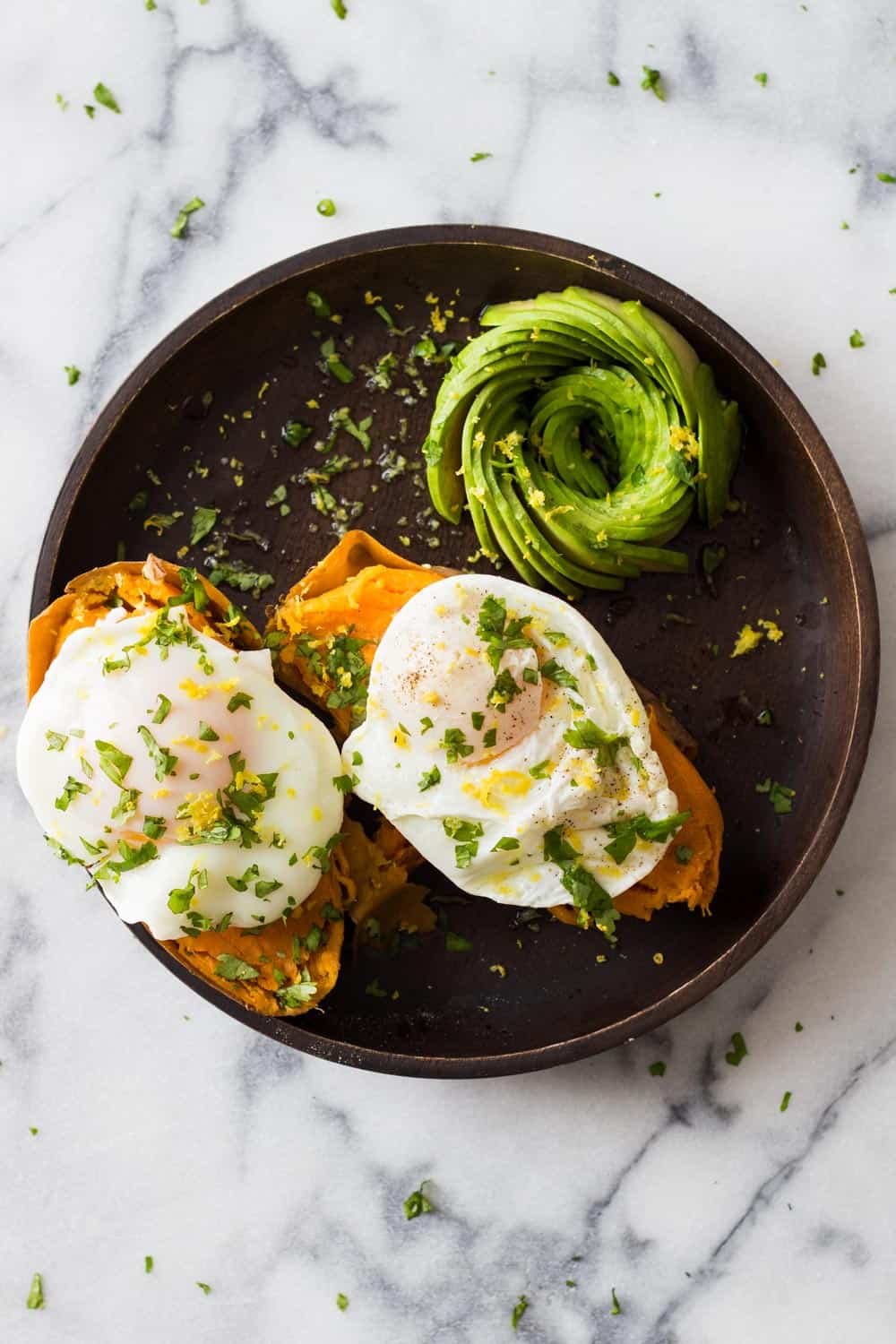 Two instant pot sweet potatoes with a poached egg on top and sliced avocado on the side, sprinkled with herbs, served on a brown plate.