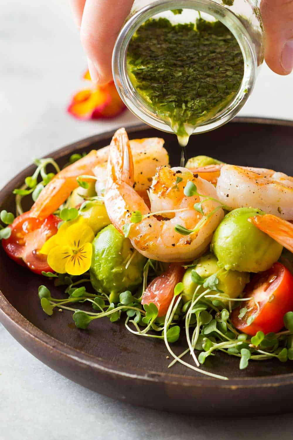 Shrimp, avocado, tomato, arugula and grapefruit on a plate with cilantro dressing being poured on it.