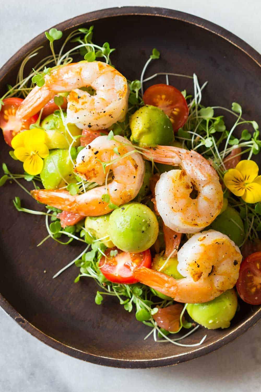 Shrimp, avocado, tomato, arugula and grapefruit with cilantro dressing served on a brown bowl.