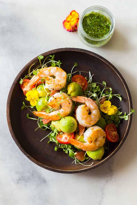 Shrimp, avocado, tomato, arugula and grapefruit on a plate with cilantro dressing in a jar.