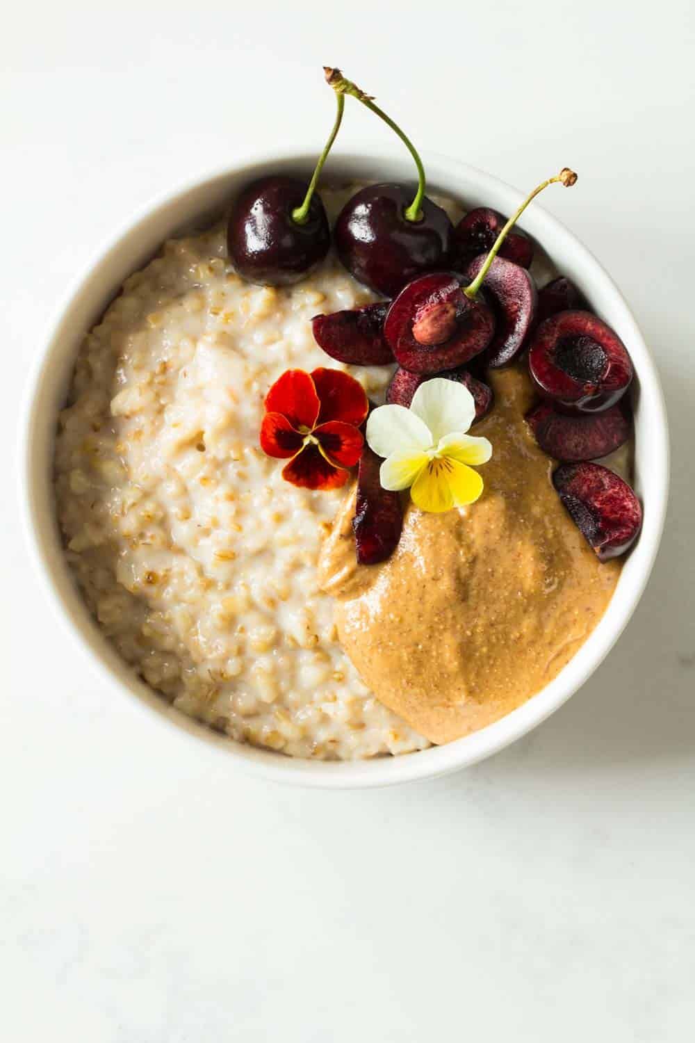 Instant pot steel cut oats topped with almond butter and cherries, served in a white bowl.