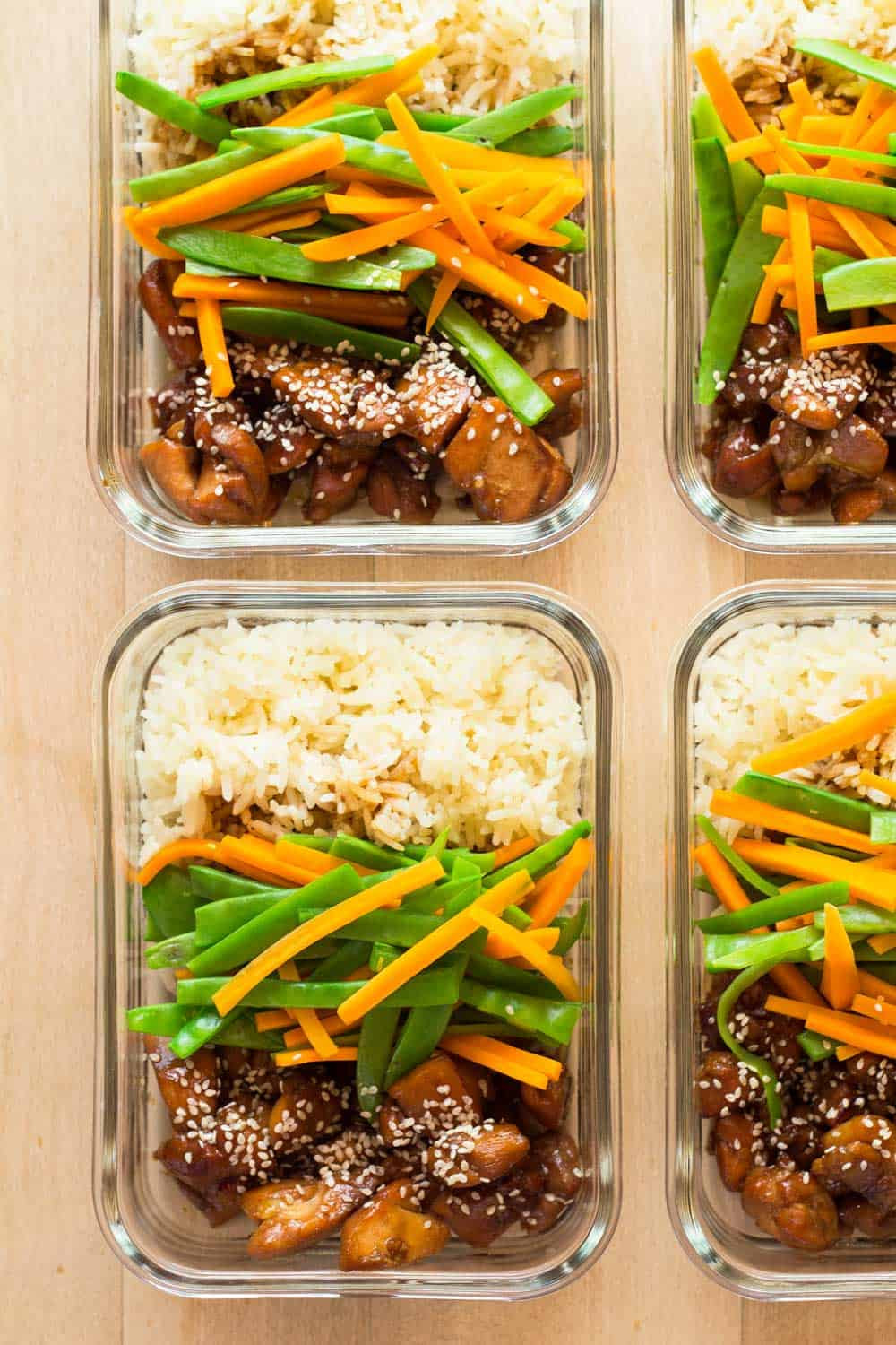 Four meal prep bowls with vietnamese chicken, veggies and white rice