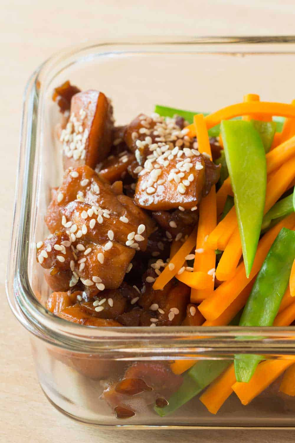 Close up of meal prep bowl showing texture of vietnamese chicken sprinkled with sesame seeds and veggies on the side
