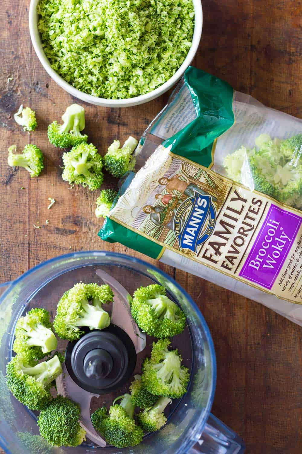 Bowl of broccoli rice, an opened bag of Mann's broccoli florets, and some broccoli florets shown inside a food processor.