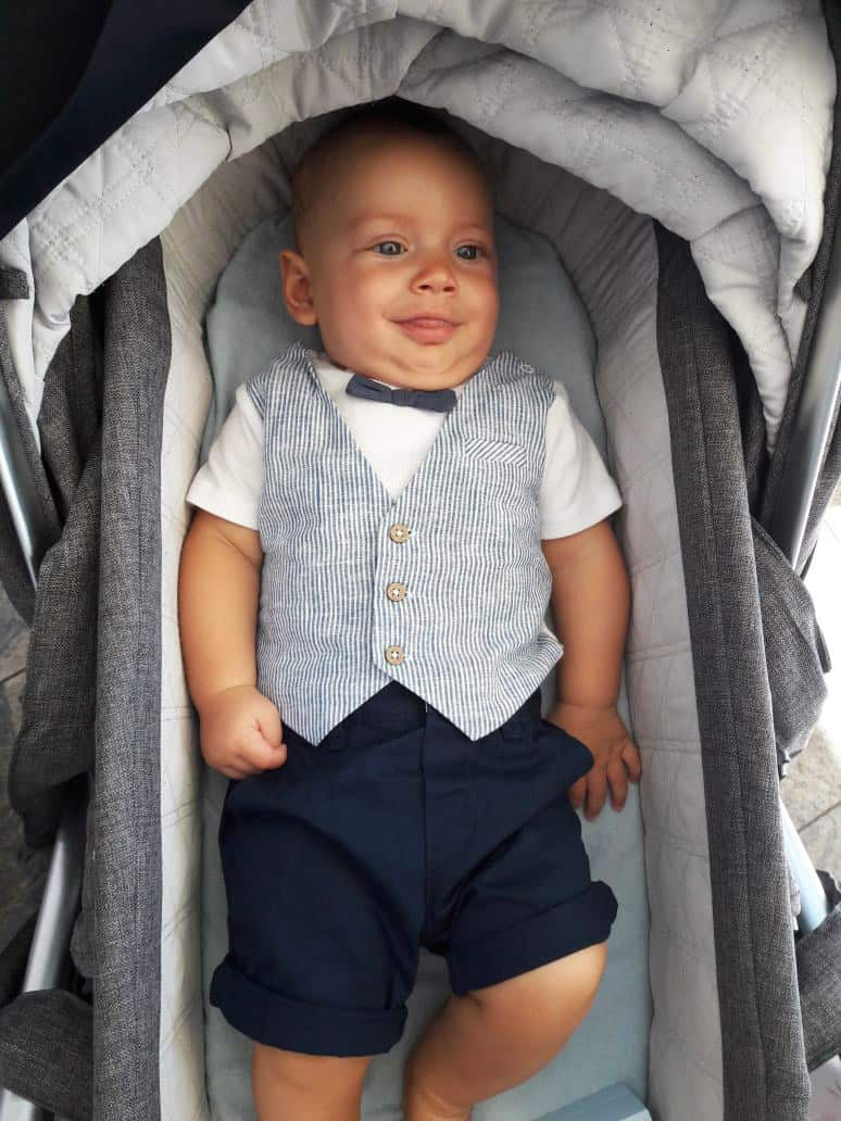A dressed-up baby in a bassinet.