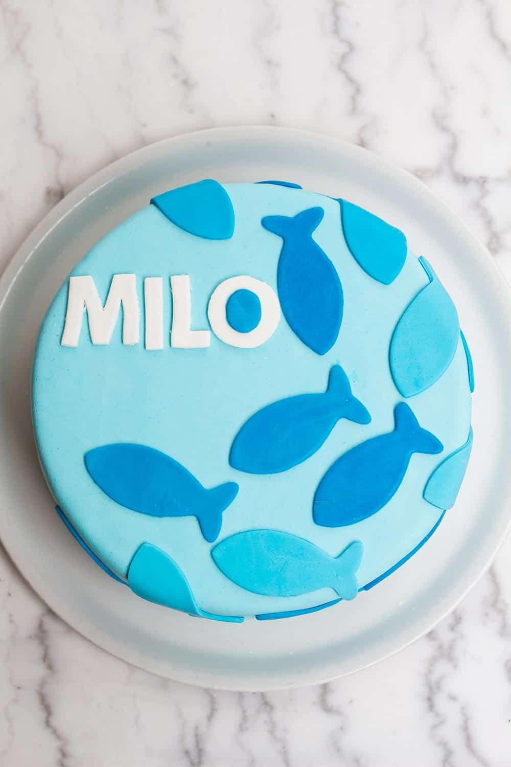 A blue cake decorated with blue frosting fish and the name Milo.