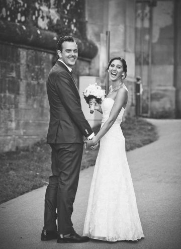 Black and white photo of a couple smiling on their wedding day.