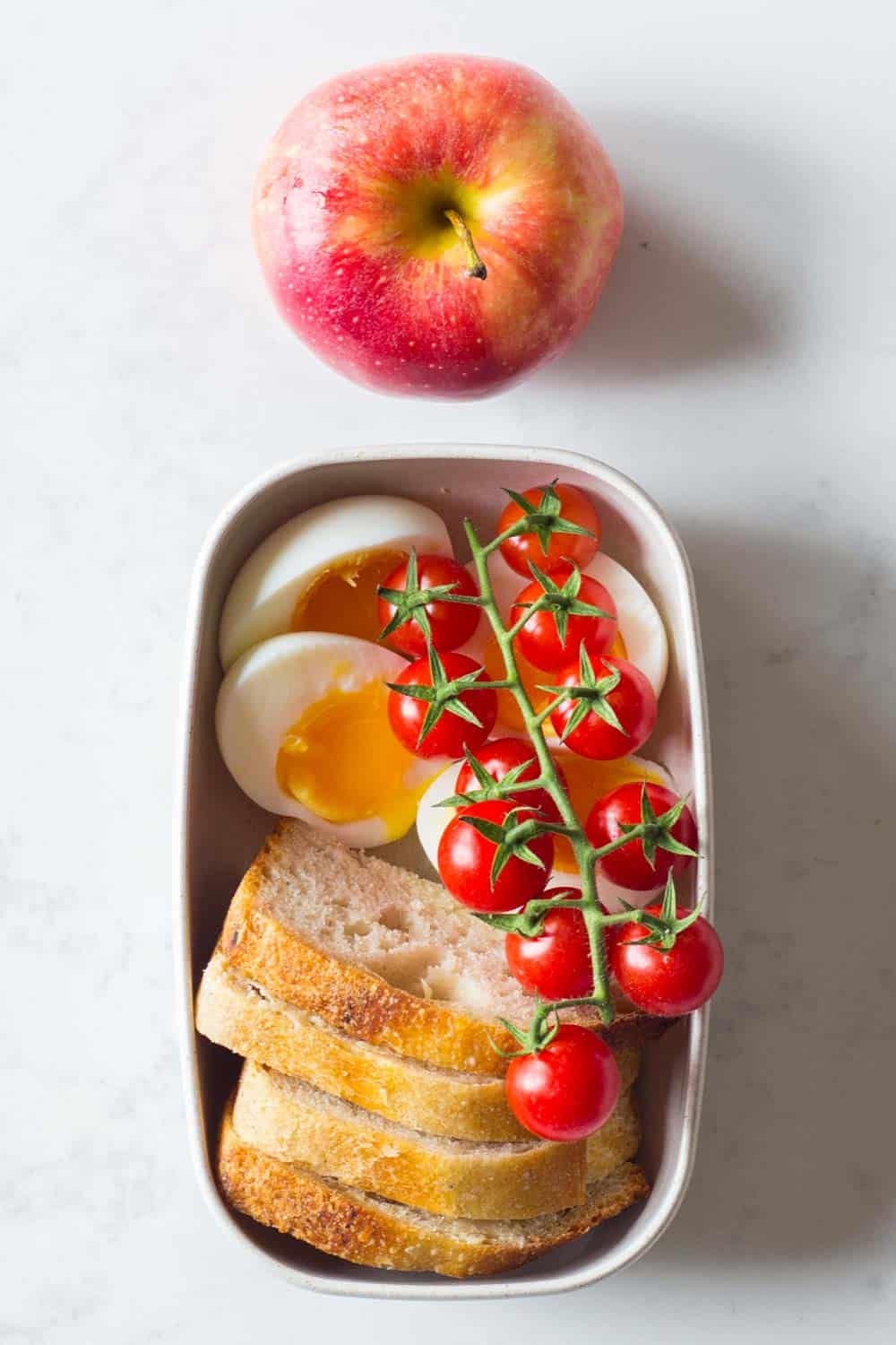 Clean Eating Breakfast for a Clean Eating Meal Plan - soft boiled eggs, buttered sourdough bread, cherry tomatoes and an apple.