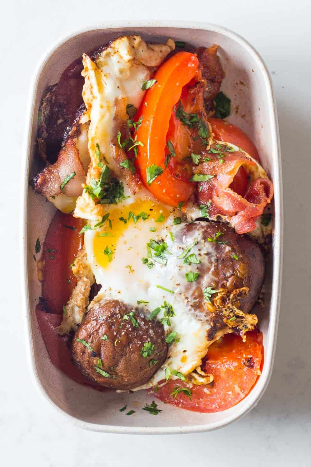 A healthy Paleo breakfast for your Paleo Meal Plan - bacon, tomato, mushrooms, eggs and parsley.