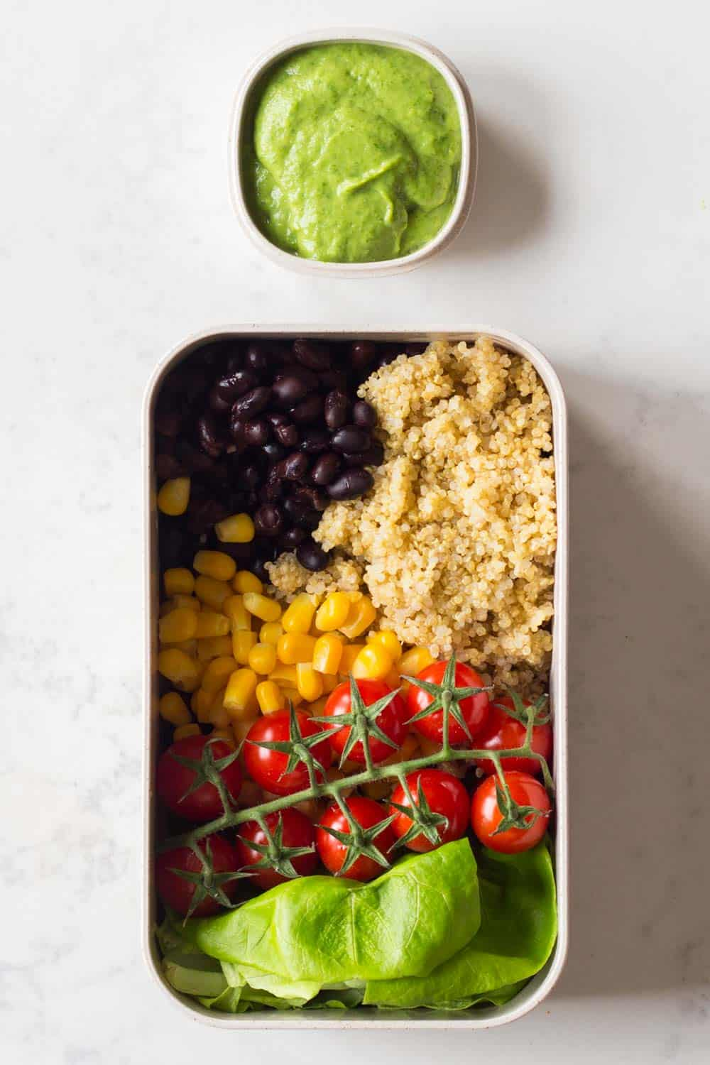 A Vegan Lunch for a Nutritionally-Balanced Vegan Meal Plan - black beans, quinoa, corn, butter lettuce and cherry tomatoes with an avocado cilantro dressing.